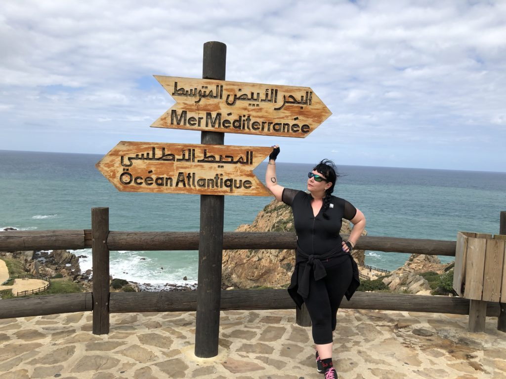 Liisa poses in Tangiers with signs for the Atlantic Ocean and Mediterranean Sea.