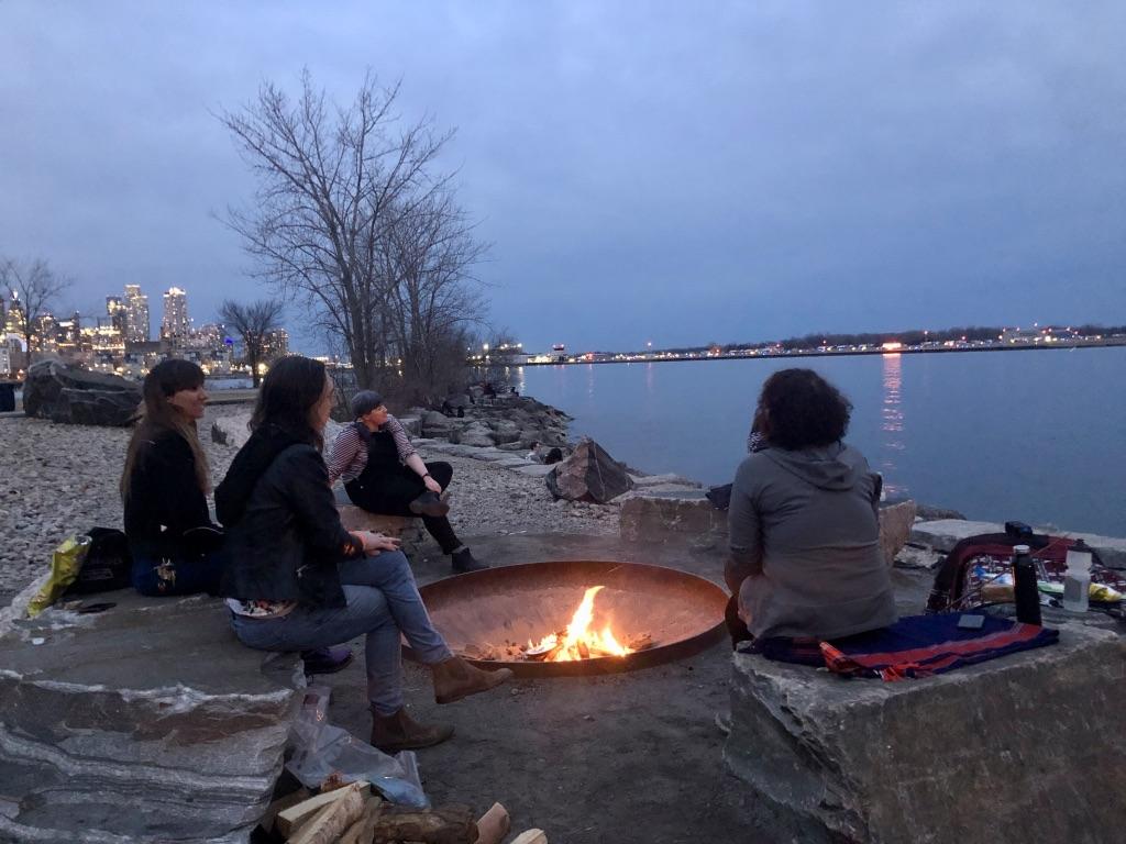 Friends at a bonfire at Trillium Park in Toronto
