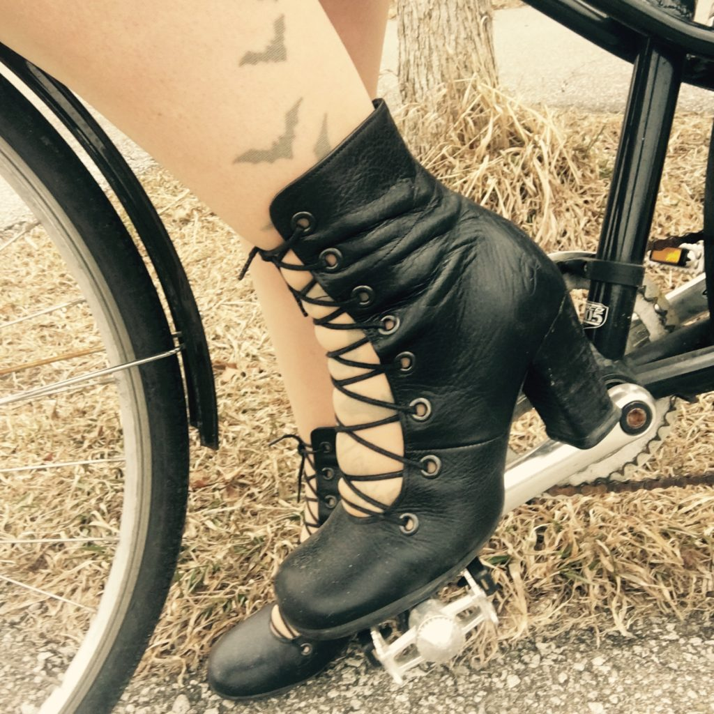 Woman's high heel boot on a bicycle pedal.
