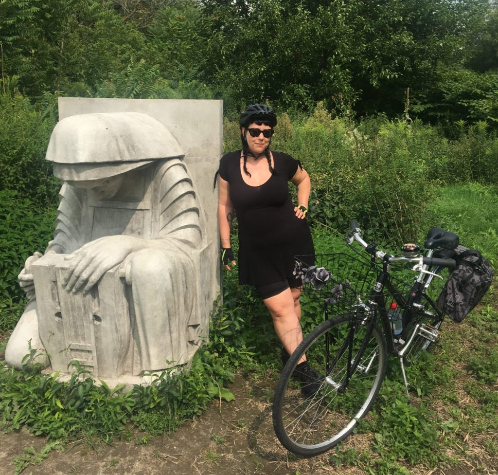 Women stops while cycling in Toronto to pose with Gargoyle sculpture on the Don River Valley bike trail