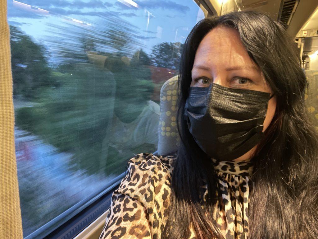 Liisa riding the Via Rail train wearing a mask