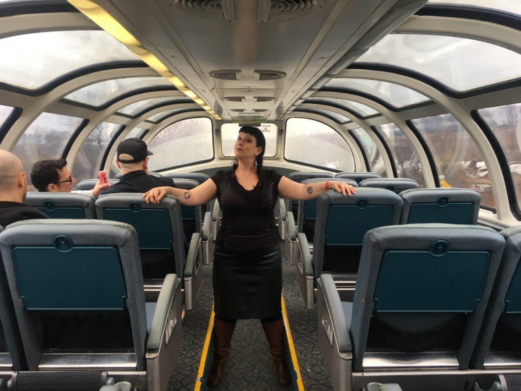 Liisa poses on the dome car of a Via Rail train