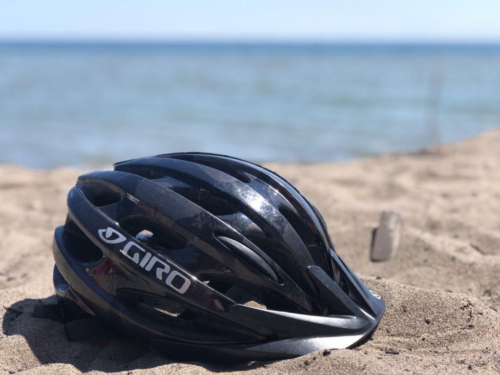 Bike helmet resting on beach sand in Toronto