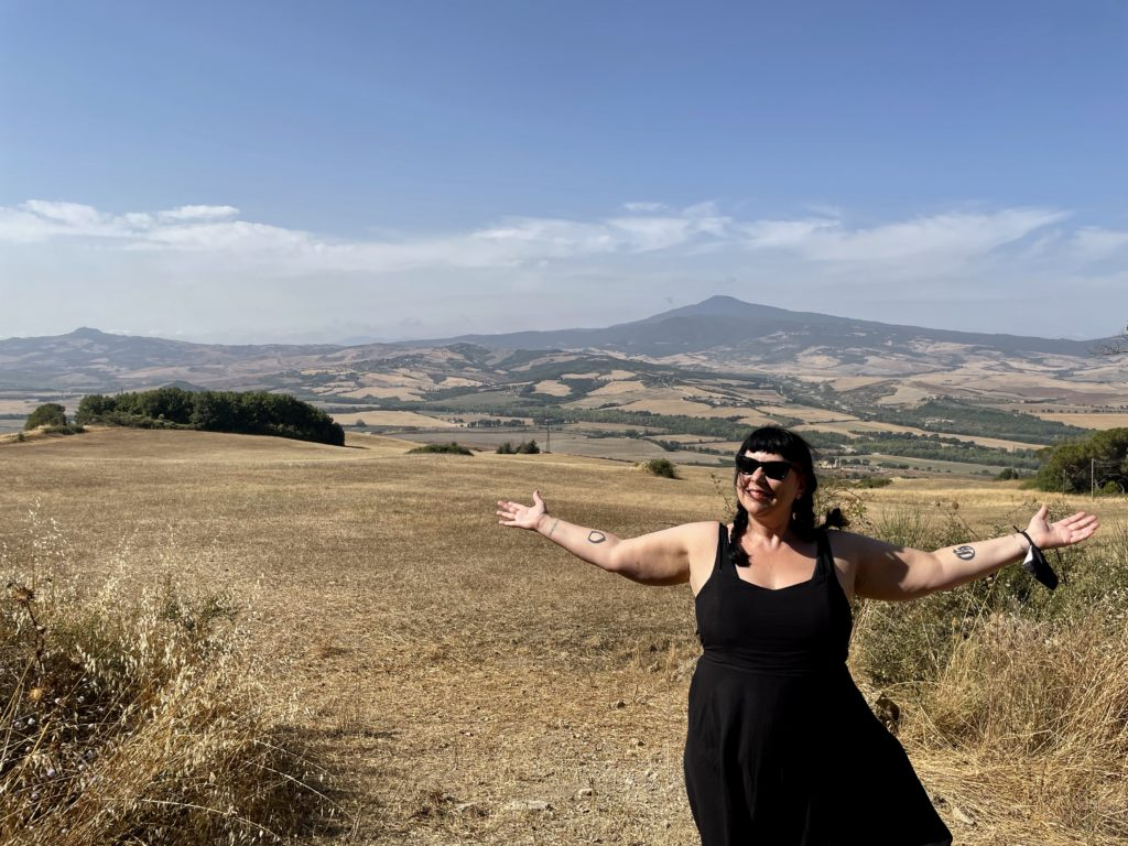 Liisa standing on a hill overlooking Tuscany Italy